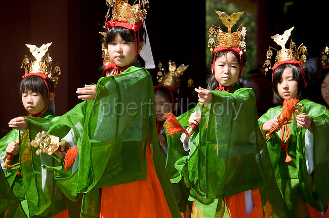 """Young """"yaotome"""" female performers perform a traditional dance outside the main hall of Tsurugaoka Hachimangu shrine during the second day of the 3-day Reitaisai grand festival in Kamakura, Japan on  15 Sept. 2012.  Photographer: Robert Gilhooly"""