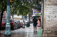 Man holding umbrella walks down 6th street, central bar entertainment district, on a wet rainy day in downtown Austin, Texas - Stock Image.