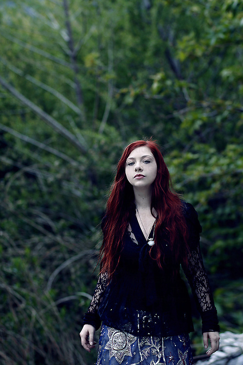 A girl with red hair alone in the forest with trees behind her.
