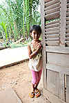 A young girl stands shyly against the door of a countryside home in the Mekong Delta near My Tho, Vietnam. <br /> Oct. 3, 2011.