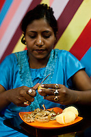 Razia Shabnam (in blue) is peels potatoes to prepare lunch for her son at home in Ekbalpore, Calcutta, West Bengal, India. Razia Shabnam, 28, was one of the first women boxers in Kolkata. She was also the first woman in her community to go to college. She is now a coach and one of only three international female boxing referees in India.  Photo by Suzanne Lee for Panos London
