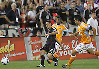 Jed Zayner #12 of D.C. United sends a pass away from Corey Ashe #26 and Brian Ching #25 of the Houston Dynamo during an MLS match at RFK Stadium in Washington D.C. on September  25 2010. Houston won 3-1.