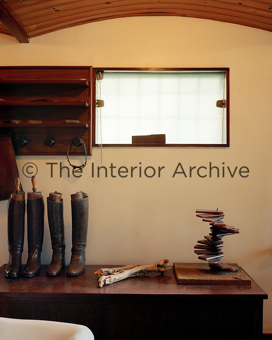 Pairs of riding boots are amongst the objects displayed on a wooden trunk beneath the barrel ceiling of the studio
