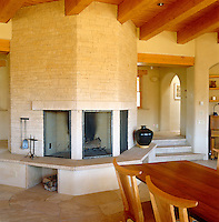 The warm tones in the dining room of this contemporary adobe house in New Mexico come from the local stone used to construct the fire-stack, the Arizona stones in the flooring and the pine beams of the ceiling