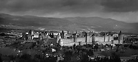 Panoramic view of the Citadel of Carcassonne, 13th century, and surrounding landscape, Carcassonne, Aude, France, pictured on February 24, 2007, on a cloudy winter morning. The two outer walls of the concentric fortified city are defended by towers and barbicans, and a draw bridge across a moat leads to the keep of the castle. Carcassonne was a stronghold of Occitan Cathars during the Albigensian Crusades but was captured by Simon de Montfort in 1209. He added extra fortifications and Carcassonne became a citadel on the French border with Aragon. The fortress was restored in 1853 by Eugene Viollet-le-Duc. Today it is a UNESCO World Heritage site. Picture by Manuel Cohen.