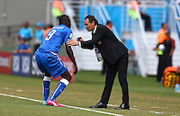 Italy coach Cesare Prandelli checks Mario Balotelli is ok after he suffered a fall