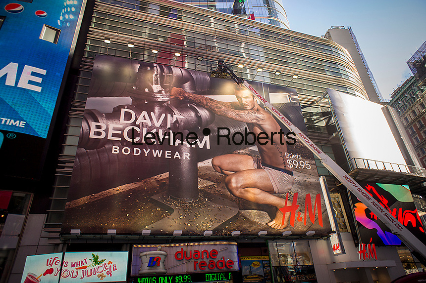 Workers install a giant blow-up of soccer star David Beckham in his branded skivvies promoting his line of underwear, gracing the side of the new Times Square H&M in New York on Friday, January 24, 2014.  H&M is once again carrying the soccer athlete's underwear collection as it did in 2012. The promotion for the line of undies will officially kick-off with a Super Bowl commercial featuring the well-exposed athlete. The store has also featured mass-market fashion by designers Versace, Karl Lagerfeld, Stella McCartney among others.  (© Richard B. Levine)