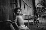 Batek Negrito boy leans against bark sided hut, Taman Negara, Malaysia.