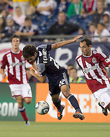 New England Revolution midfielder Benny Feilhaber (22) gets disrupted as he dribbles. In a Major League Soccer (MLS) match, Chivas USA defeated the New England Revolution, 3-2, at Gillette Stadium on August 6, 2011.