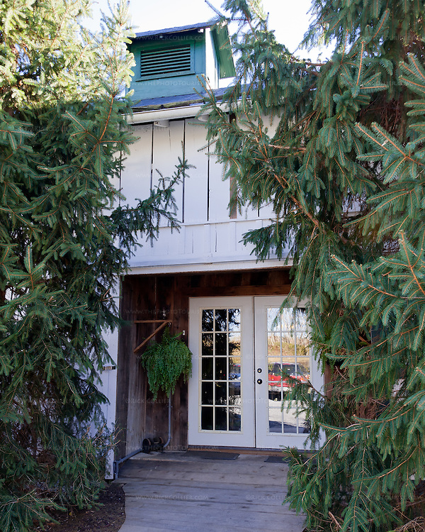 The front door at Aspen Dale Winery is flanked by enormous evergreen trees.