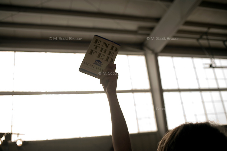 "A man holds a copy of Ron Paul's book ""End the Fed"" after a Ron Paul rally at Jet Aviation in Nashua, New Hampshire, on Jan. 6, 2012.  Paul is seeking the 2012 GOP Republican presidential nomination."