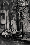 a black and white photography of a street lamp & bicycles sitting outside of St John's college, Cambridge on a cold wet winter afternoon