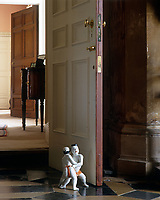 A figurine of a pair of sumo fighters is used as a door stop in this hallway