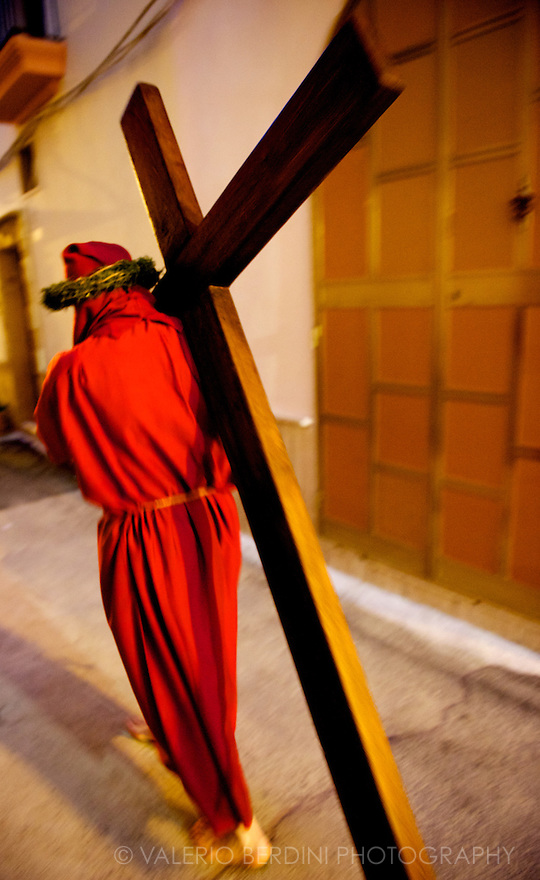 A penitent walks the path barefooted, carrying the cross as a way to repent his sins