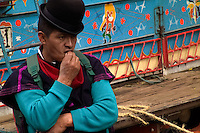 A Guambiano man waits in front of a colorfully painted Chiva bus during the traditional Indian market in Silvia, Colombia, 8 April 2004. The Guambiano, a South American Indian tribe, live in the southwestern corner of Colombia. There are about 20.000 of Guambianos living in communities close to their capital town of Silvia. Guambianos are traditionally agricultural people. Since the Spanish conquest they have been gradually evicted from their original fertile lands up to the cold, rainy mountains. In spite of the permanent pressure by Colombian society, the Guambiano Indians still speak their original language, keep their colorful clothes and maintain their nature based religious customs.