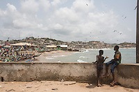 Ghana - Cape Coast - Local boys stand on the terrace of the castle overlooking the harbour. Originally built in 1653, this UNESCO World Heritage Site Castle served as one of the most important slave trading posts along the West Africa coast. Today, it is one of the main attractions in Ghana, with around 90,000 tourists vising it every year. According to environmental experts, much of the West African coast could be submerged by 2099 as a direct consequence of rising sea levels and climate change.