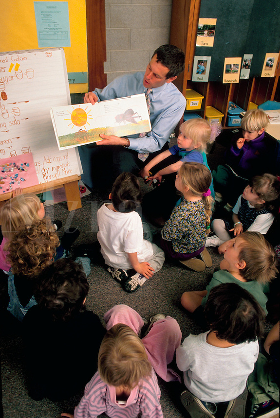 A treacher reads a story to a group of preschoolers in a classroom.