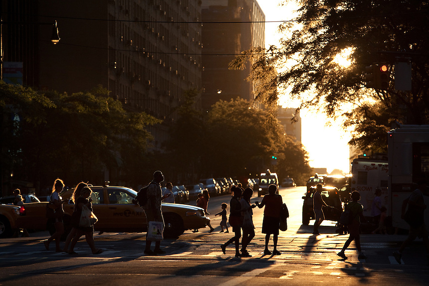 People walk across 57th and 8th Ave as the sun sets across Columbus Circle in New York on June 23, 2012.