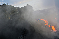 People watching river of molten lava flowing to the sea, Kilauea Volcano, Hawaii Islands, United States