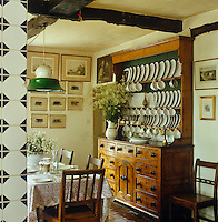 A large dresser laden with a collection of crockery takes pride of place in this country dining room
