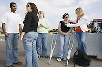 USN Sailors Kate Wilson (R) of Buffalo, New York and Rachel Blomstrom of Houston Texas who are attached to the Fleet Anti-Submarine Warfare Training Center in Point Loma San Diego California wait to leave the center with Sharon Roberts (C) of San Diego for Thanksgiving Day Dinner at Roberts home on, Thursday November 22, 2007.  Rebecca McLaughlin (second from L) of the Armed Services YMCA pairs sailors who would otherwise spend the holiday alone with local families as part of the Adopt-A-Sailor Program.  Roberts was offering to take additional sailors home if needed and volunteer Gauraw Patel (L) found another two young sailors who had not been paired up with anyone yet.  The San Diego Armed Services YMCA has organized the program for San Diego based sailors every year for the past 65 years .  Blomstrom had injured her foot at a music concert the previous Sunday.