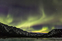 Aurora borealis swirls over the overflow ice along fossil creek in the White Mountains National recreation area in interior Alaska.