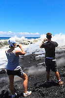 A couple captures the moment in pictures of lava meeting the ocean at Fox's Landing on the Big island.