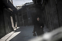 A Syrian Muslim woman walks on the empty streets at the Old City neighborhood of Bab Al Naser, a commercial distric in the downtown area under control of the opposition fighters where skirmishes with the Assad's army take place at any moment.