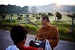 A jungle monk living in the Thai countryside accepts alms from a lay Buddhist near Saraburi, Thailand. &quot;Jungle&quot; or &quot;forest&quot; monks focus on the study of meditation and devote themselves to more traditional ascetic practices  away from urban areas. They are sometimes considered more pure in their discipline and devotion to Theravada Buddhism than city monks, who are primarily scholars and civic figures.