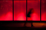 A person walking in a blurred motion against windows with red light.
