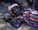 Turkana man sleeping on his head / footstool, Northern Kenya