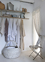 Towels hang from a simple wooden shelving unit and a  length of fabric acts as a door into the bathroom