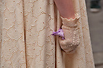 A woman wears an eyelet dress and delicate gloves to the Easter Parade in New York City on Fifth Avenue
