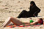 Cooling off at Venice Beach as a record of 92 degrees was set in downtown Los Angeles today, according to the National Weather Service breaking a 45 year old record. A muslim woman wearing the traditional hijab sitting on the sand next to a woman waering a bikini and wotking on a suntan