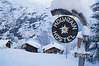 Snow covered sign for mountain hostel in Swiss Alps