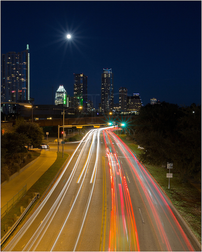 This vertical oriented photograph shows the Austin skyline taken from Lamar Bridge. The headlights and tailights were exaggerated using a long exposure as cars sped along Caesar Chaves heading home after a long day of work downtown.