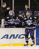 Adam Schmidt (HC - 14) is congratulated at the Crusaders bench. - The Bentley University Falcons defeated the College of the Holy Cross Crusaders 3-2 on Saturday, December 28, 2013, at Fenway Park in Boston, Massachusetts.