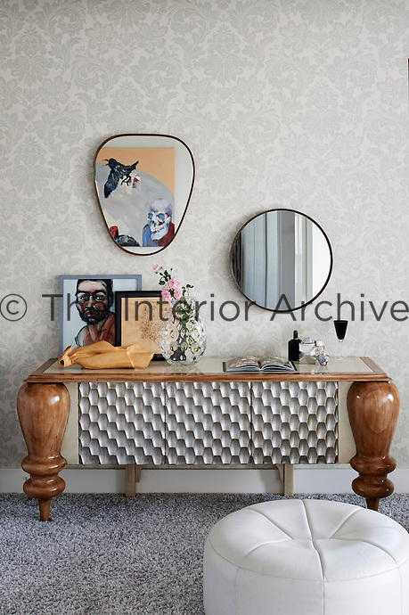 A fabulous furniture piece from Lola Glamour displays a wood sculpture by Michaelis graduate Adriaan Alkema, a painting by Leon Vermeulen and a pen sketch by Sam Allerton. A work by Lance Friedlande is reflected in the Art Deco mirror.