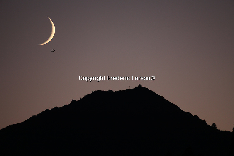 The crescent moon set behind Mount Tamalpais during twilight as seen from San Rafael, CA.