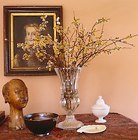 A vase of catkins conceals a small period portrait above a carved wooden bust and other objects on top of a dresser