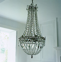 An antique crystal chandelier is suspended in the centre of an all-white dining room