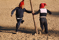 Aymara Indian children playing, running around a pole, Suriqui Island, Lake titicaca, Bolivia.