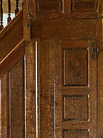 A detail of the panelled staircase in the entrance hall shows the rich patina of the small door to the understairs cupboard and its original iron hinge