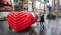 """Viewers engage with """"HeartBeat"""" in Times Square in New York on Monday, February 9, 2015 by playing the various percussion devices built into the interactive sculpture. Designed  by Stereotank, the heart shaped sculpture gives off an audible heartbeat as visitors counterpoint it with their own percussion. This is the seventh installation for Valentines Day and it is tied in with the """"Love in Times Square"""" promotion offering discounts on restaurants, hotels and other entertainment.  The installation will be on display until March 8. (© Richard B. Levine)"""