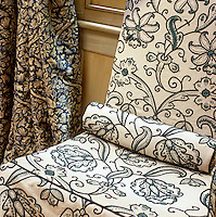 The embroidered Arts and Crafts-style fabric of the loose covers on an antique chair forms a subtle contrast to an adjacent curtain in a similar blue-and-white print