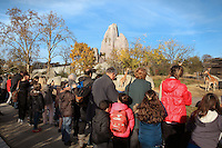 Visitors watching West African giraffes (Giraffa camelopardalis) in their open outdoor enclosure with the Grand Rocher or Great Rock in the background, in the Zone Sahel-Soudan of the new Parc Zoologique de Paris or Zoo de Vincennes, (Zoological Gardens of Paris or Vincennes Zoo), which reopened April 2014, part of the Museum National d'Histoire Naturelle (National Museum of Natural History), 12th arrondissement, Paris, France. Picture by Manuel Cohen