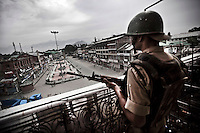 An Indian paramilitary soldier stands guard on a balcony at Lal Chow area in Srinagar during a curfew. Beyond being the contested territory between India and Pakistan, Kashmir has seen 22 years of struggle between residents and the Indian administration. Since the early years of the conflict the Indian rule has deployed more than 800,000 troops in Kashmir and the valley is constantly declared under curfew. Srinagar, Indian administrated Kashmir.