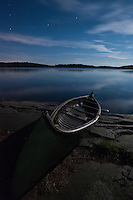 A traditional cedar strip and canvass Old Town canoe on the granite shores of David Lake, by moonlight.