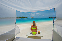 Maldives, Rangali Island. Conrad Hilton Resort. Woman sitting in canopy chair on the beach. (MR)