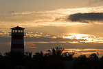 Grand Bahama Island, The Bahamas; Lucaya Lighthouse in silhouette with cloud formations lit up by sunrise in the background
